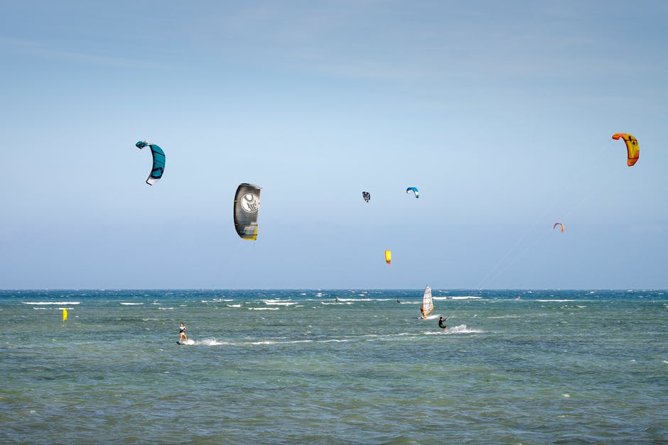 A group of people flying kites in the ocean