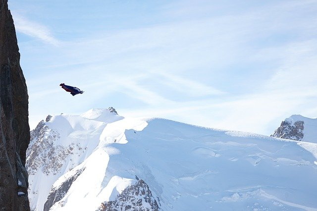 A man flying through the air on a snow covered mountain