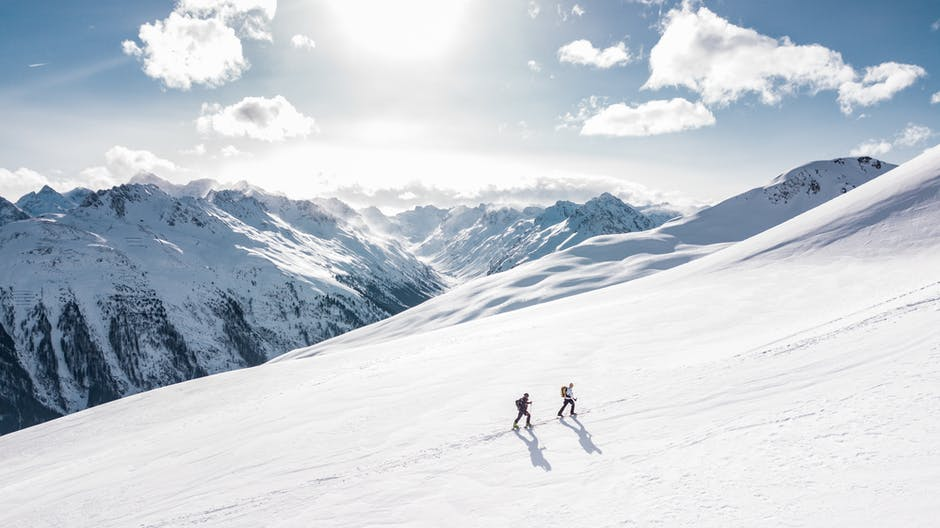 A man riding skis down a snow covered mountain
